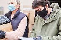 Lieferdienst Team mit Mundschutz prüft Paket Lieferungen