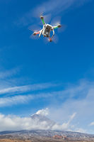 Flying drone quadcopter UAV aerial videography in sky on background of volcano eruption