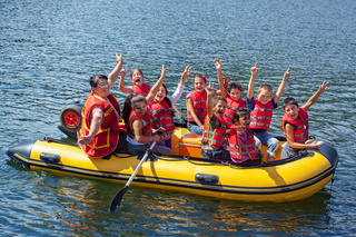 Happy children in a boat on the lake waving