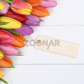 Tulpen Blumen im Frühling oder Muttertag mit leerer Karte auf Holzbrett