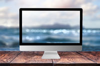 Computer display with blurred sea background.