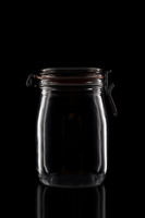 A glass canning jar isolated on black with reflection.