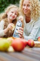 Mutter und Tochter reiben Apfel für Kuchen