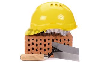Ziegelstein und Werkzeug als Symbol für Hausbau