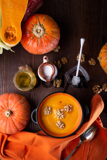 baked pumpkin cream coup with, nuts ,  coconut milk and natural honey served in nice bowl. served at wooden brown table with ripe orange  pumkins. flat lay. healthy life concept