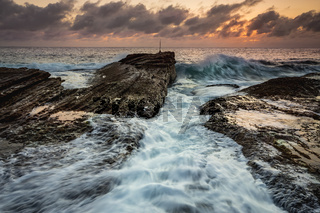 Waves crash as sunrise dawns over the ocean