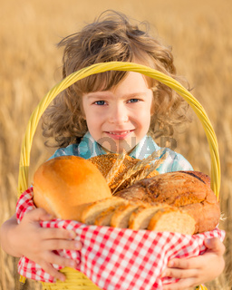Child holding bread in basket