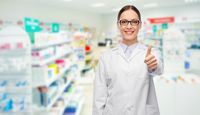 female pharmacist showing thumbs up at pharmacy