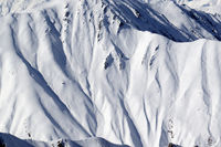 High mountains with sunlit snowy slope at cold winter day