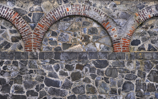 Old quarry stone wall with brick ornaments