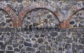 Alte Bruchsteinmauer mit Ziegelornamenten