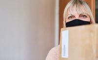 Frau mit Mundschutz und Paketen vor Wohnungstür