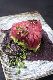 Gourmet fish tartar raw from tuna fillet with hashed avocado