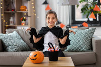 girl in halloween costume with bat cape at home