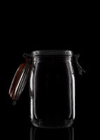 A glass storage or canning jar isolated on black with reflection, with lid open.