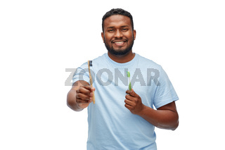 african man with wooden and plastic toothbrushes
