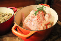 Closeup of a raw chicken and stuffing in a pot