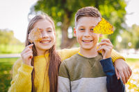 Happy Caucasian siblings enjoying in autumn day in park, sunny weather. Kids having fun holding fallen yellow leaves in nature. Funny twins in autumn park. Autumnal mood. Teenagers posing embracing