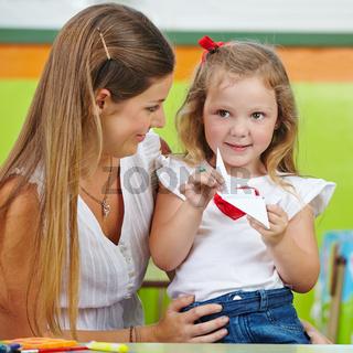 Mädchen bastelt Origami mit Mutter