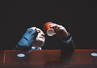 Low angle on mature business man in a business suit, holding a disposable cup of coffee in a office building having a business conversation on the phone. Business concept