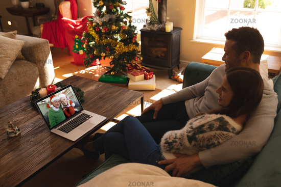 Couple sitting on couch having a videocall with senior couple in santa hats smiling on laptop at hom