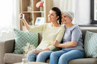 senior mother with daughter taking selfie at home