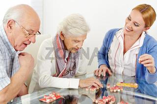 Senioren spielen Bingo mit Altenpflegerin
