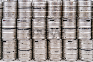 Wall of used and scratched stainless steel beer barrels or kegs