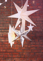 Decorative stars hanging against brick wall