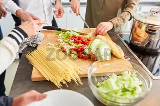 Studenten bereiten gemeinsam Salat und Pasta zu für Lunch