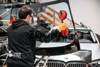 Automobile technician worker replacing windscreen or windshield of a car in auto service station garage.