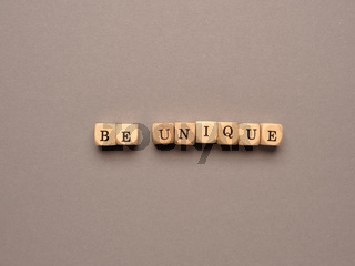 Be unique written with small wooden blocks