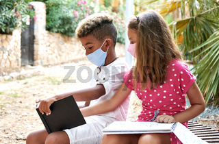 Multiethnic kids showing each other drawings outdoor