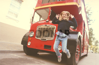 Preteen girl by the red bus