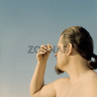 Reflection of the eye in a broken piece of mirror. Male portrait, inner self and psychology concept. Shot on analog film.