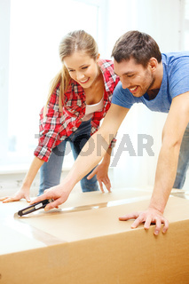 smiling couple opening big cardboard box