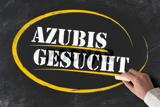 hand holding piece of chalk against blackboard with text AZUBIS GESUCHT