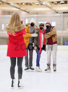 friends in masks taking photo on skating rink