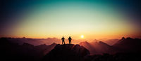Two Men reaching summit enjoying freedom and looking towards mountains sunset.