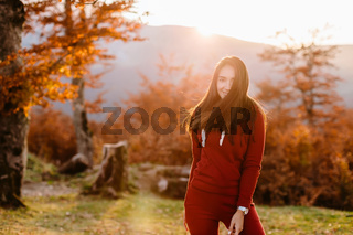 Portrait of woman in autumn forest at sunset