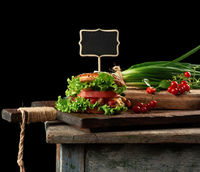 cheeseburger with minced meat, green lettuce and ketchup on a wooden brown kitchen board