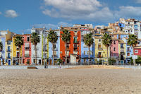 Villajoyosa sandy beach with coloful houses and palm trees. Spain