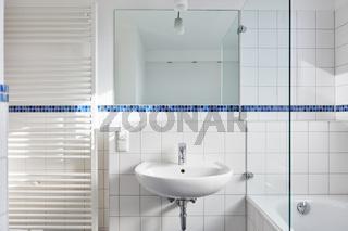 Badezimmer mit Waschbecken und Spiegel und Heizkörper