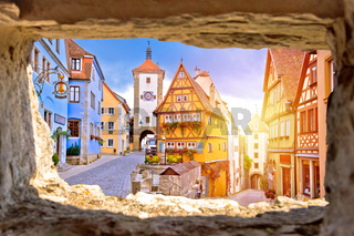 Cobbled street and architecture of historic town of Rothenburg ob der Tauber view through stone window