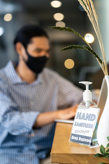 Hand Sanitizer in office with businessman wear face mask