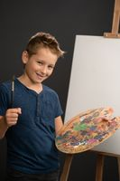 Charming caucasian 10 year old boy looks at camera holding a palette with paints on the background of an easel with canvas. School of arts concept. Vertical photo