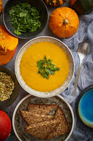 Pumpkin soup decorated with parsley for Thanksgiving, halloween. Placed on grey stone background