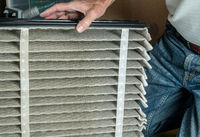 Senior man changing a dirty air filter in a HVAC Furnace