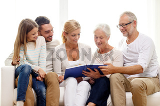 happy family with book or photo album at home