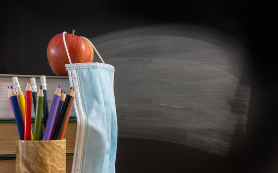 Back to virtual school background concept with stack of books, pencil, apple with face mask